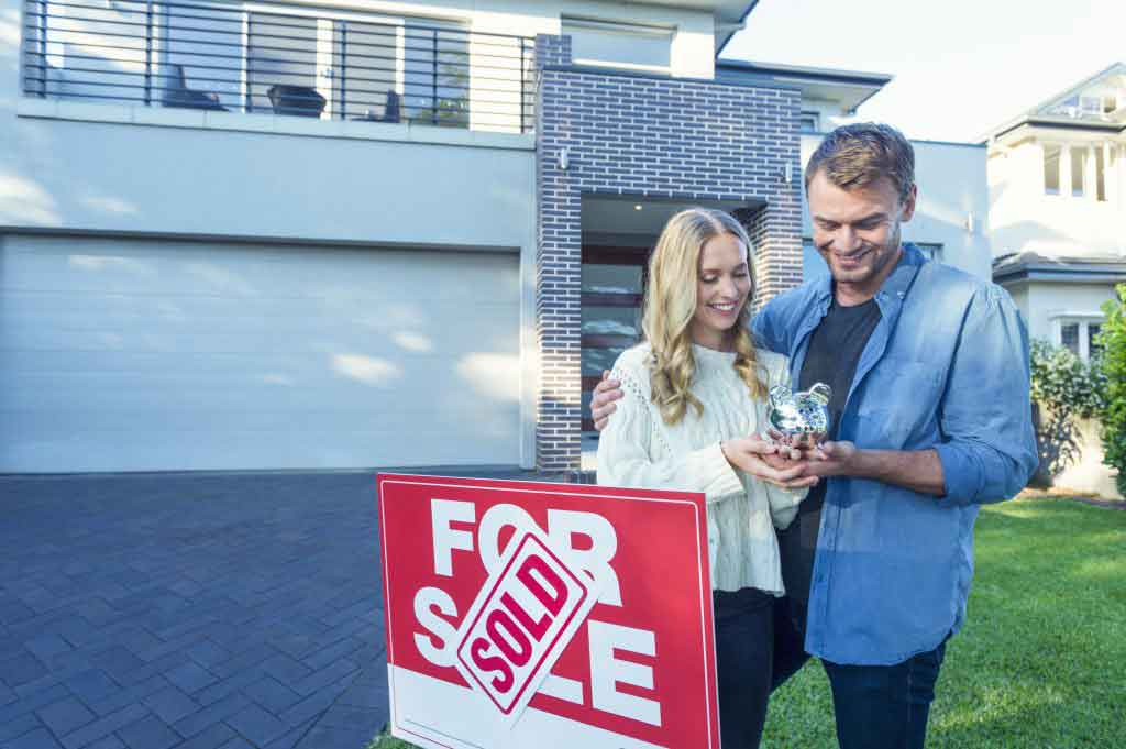 Couple holding a piggy bank in front of house. They are casually dressed standing in front of a modern house. Both look happy. For sale â?? sold Real estate sign on lawn.