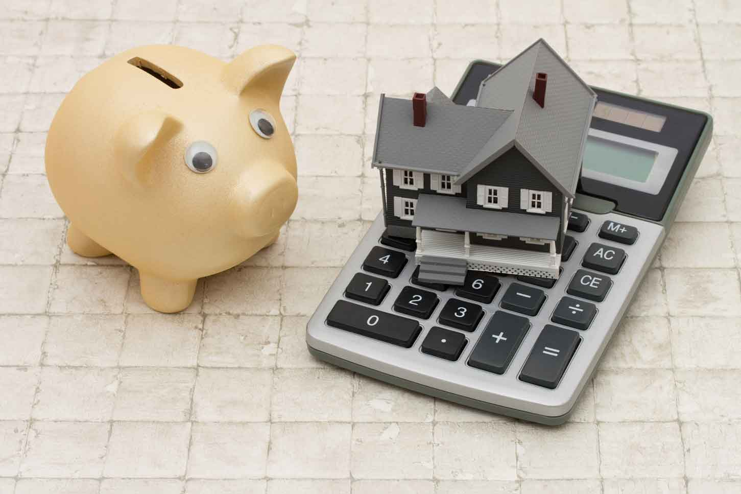 Gray house, piggy bank and calculator on stone background