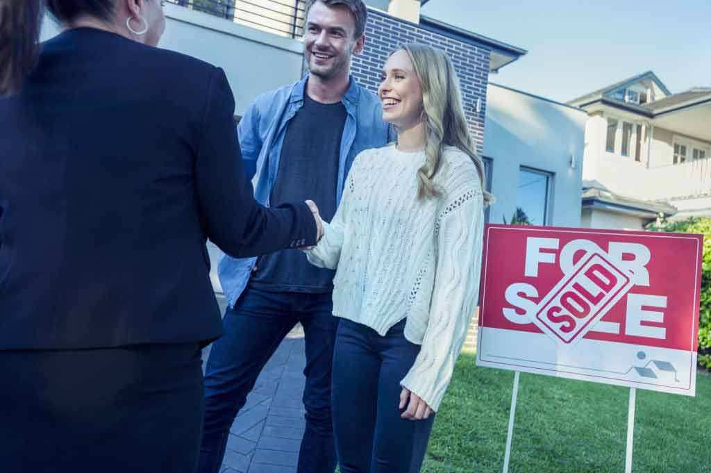 Couple standing in front of a sold home with real estate agent.