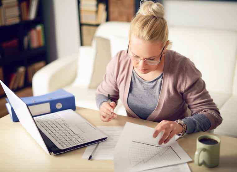 A blonde lady working on papers next to a laptop