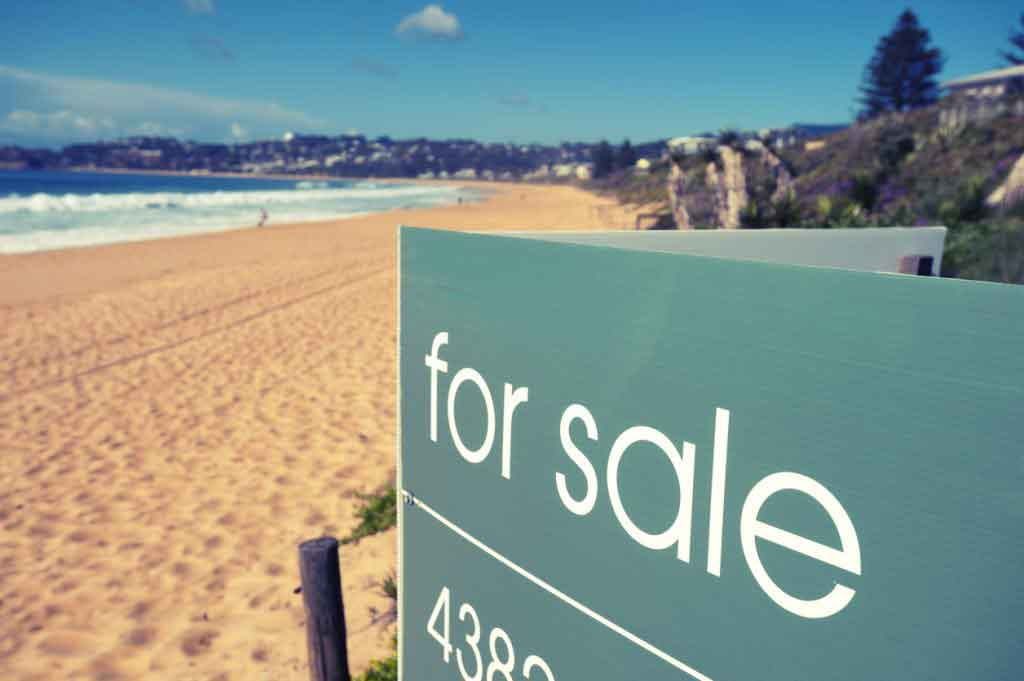 Real estate for sale sign on a beach